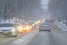 Cars Drive During A Snowfall On A Snowy Street In The City In The Evening. Soft Focus