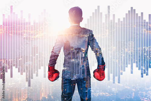 the double exposure image of the businessman wearing a boxing mitts overlay with cityscape image Canvas Print