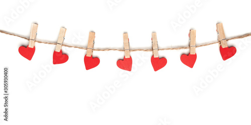 Photo Clothes pegs and red wooden hearts on rope isolated on white background