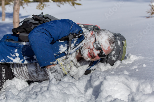 Fotografie, Obraz Hiker in sunglasses with backpack lay down with snow on his face in winter