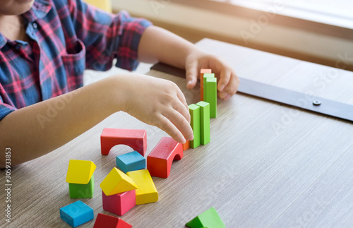 Photo Creative concept; The boy plays colorful wooden blocks at home.