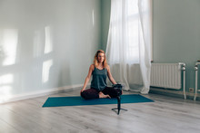 Young Woman Blogger Recording Herself Doing Yoga Using A Phone With Gimbal - Social Media Star Concept