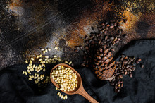 Pine Nuts In The Spoon And Pine Nut Cone. Organic Food. Black Background. Top View. Space For Text