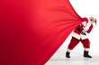 canvas print picture - Santa Claus pulling huge bag full of christmas presents isolated on white background. Caucasian male model in traditional costume. New Year 2020, gifts, holidays, winter mood. Copyspace for your ad.