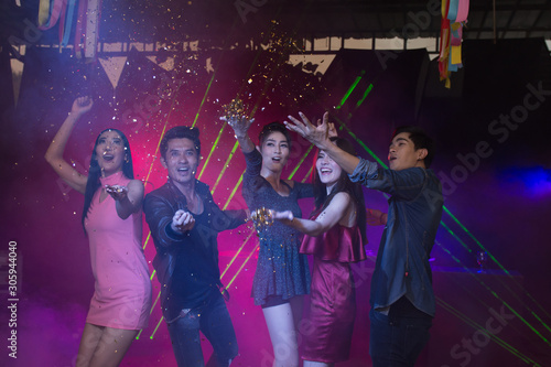 Holiday celebrations concept, Traveller people dancing together with enjoying at colourful night party club. - 305944040