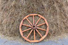 A Wooden Cart Wheel Lies On A Pile Of Straw