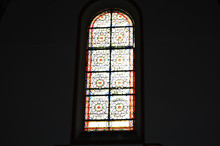 Sunlight Pours Through The Multicolored Stained Glass In The Church Against A Dark Wall, The Interior Of The Catholic Cathedral
