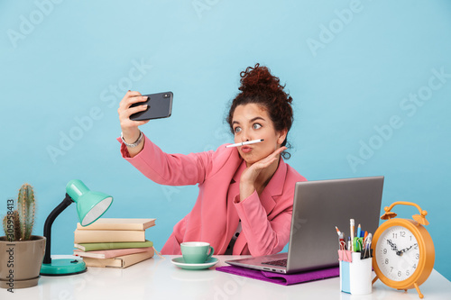 Photo Image of amusing woman taking selfie photo on cellphone and grimacing
