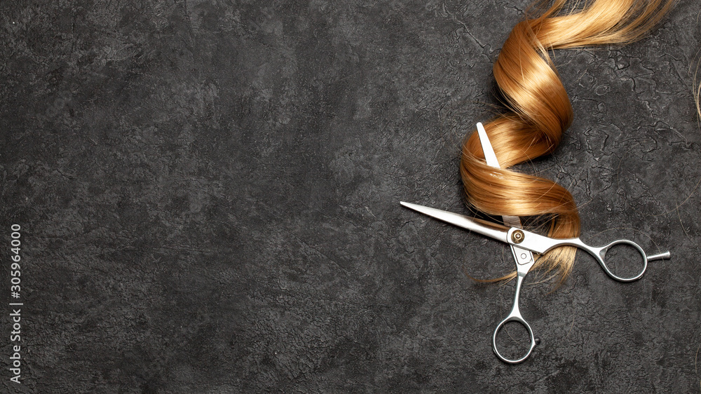 Fototapeta The hairdresser. Scissors and curl of hair on a black background