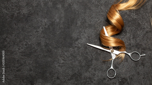 Obraz The hairdresser. Scissors and curl of hair on a black background - fototapety do salonu