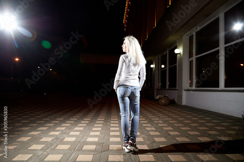 Ugly woman in the city at night with lighting flashes in the black background