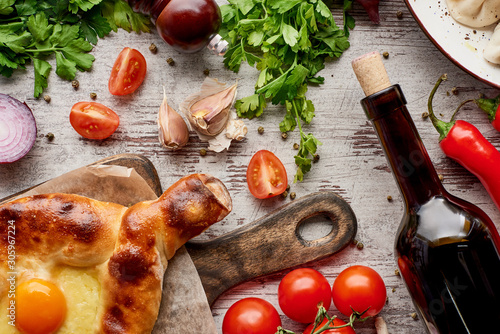 top-view-of-adjarian-khachapuri-wine-bottle-wegetables-and-cilantro-on-wooden-table