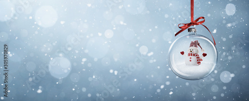 Fotografía  Happy snowman in the christmas bauble over the winter, snowy background with cop
