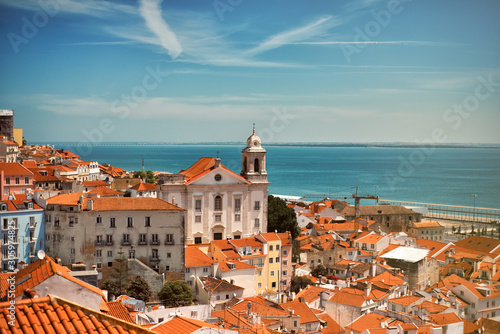 Panoramic view on the roofs of Lisbon from Alfama in the summer time with blue sky and river on background Wallpaper Mural