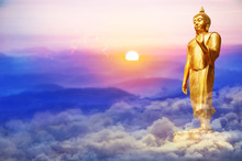 Golden Buddha Statue Standing On Soft Clouds Field With   Sunrise In The Morning And Mountain Scenery View And Twilight Sky Background