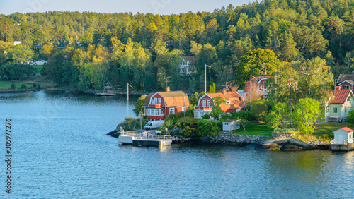 Rocky coast of Stockholm archipelago in Baltic sea with traditional white and red houses at sunny autumn evening with a fall scenery Wallpaper Mural