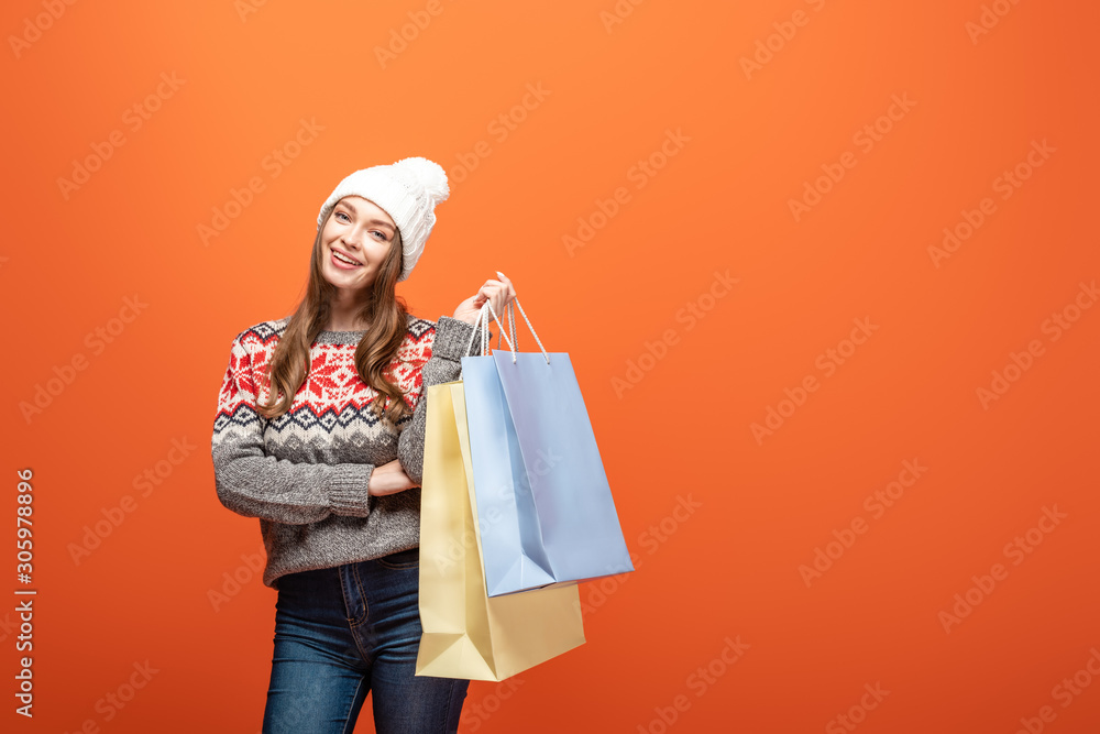 Fototapeta happy girl in winter outfit holding shopping bags on orange background