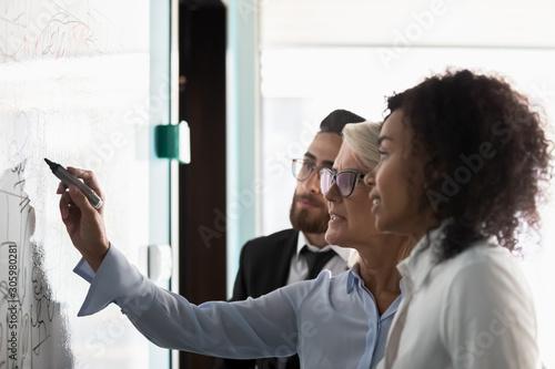 Stampa su Tela Diverse businesspeople write on board in office brainstorming