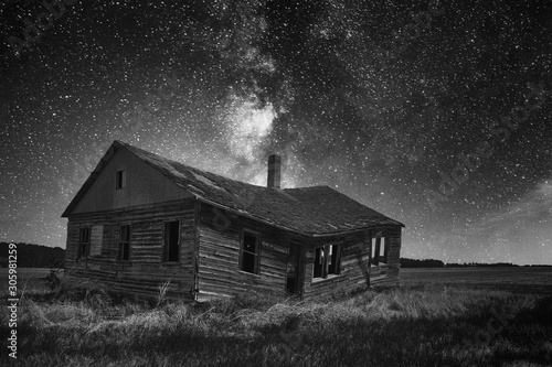Fotomural  An old weathered and faded clapboard farmhouse sagging in the middle under a sta