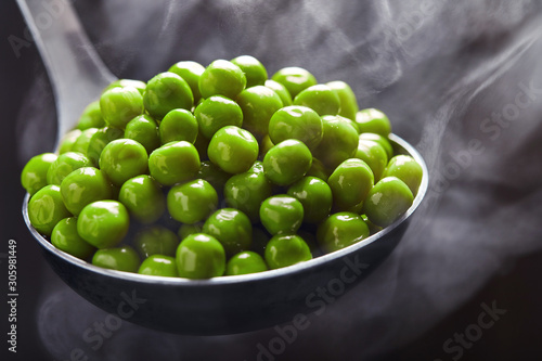 Fototapeta Green peas in a ladle with steam coming from it against a dark background. Close up obraz