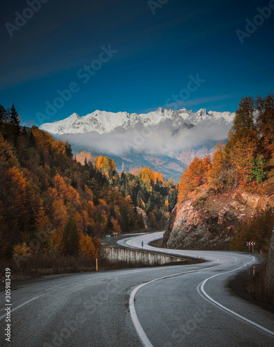 scenic view of empty road with snow covered landscape while snowing in winter season Fototapeta
