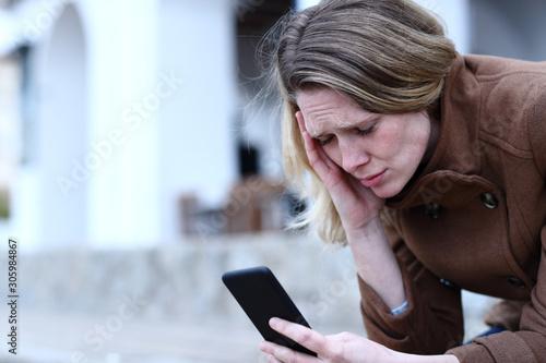 Sad adult woman reading bad news on mobile phone Wallpaper Mural