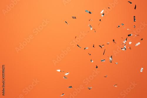shiny silver confetti on orange background