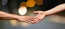 Hands Reaching Out And Touching Each Other On A Dark Background