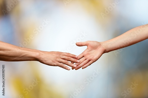 Foto Hands reaching out and touching each other on a bokeh background