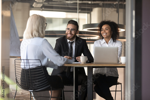 Photo Smiling multiracial employers laugh talking with job candidate in office