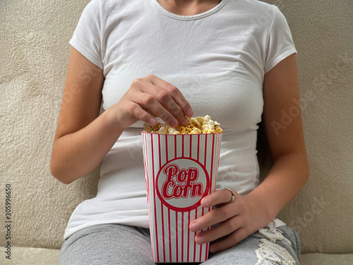 Fotografie, Obraz  Lady eating popcorn while looking at TV screen