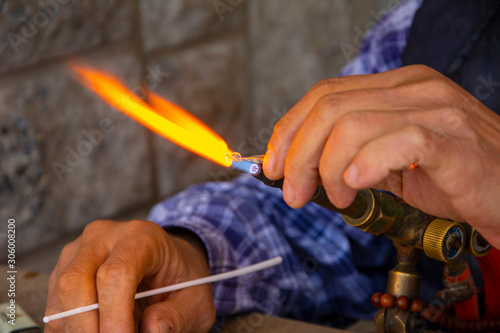 Glass artist shapes the material in his hand with fire Canvas Print