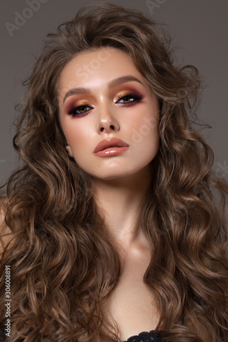 Young sexy brunette model with professional makeup, perfect skin, volume hairstyle. Colorful smoky eyes.