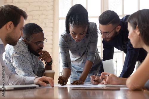 Focused arican american millennial female team leader writing notes Fototapet