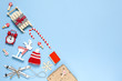 Leinwanddruck Bild - Corner creative Christmas composition. Candy cane, gift, sled, deer, hat, alarm clock, ski, clothespins, book, wooden snowflakes on blue background, copy space. Minimal style. Top view