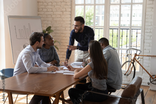 Smiling confident arabic team leader pointing at coworkers. Canvas Print