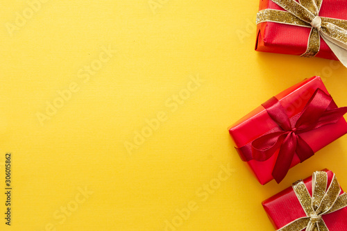 Top view of red gift boxes with ribbon over colorful yellow background. Valentine's day, Christmas or birthday concept.