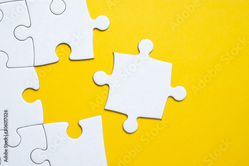 Final white piece is lying next to the jigsaw puzzle on yellow background Canvas Print