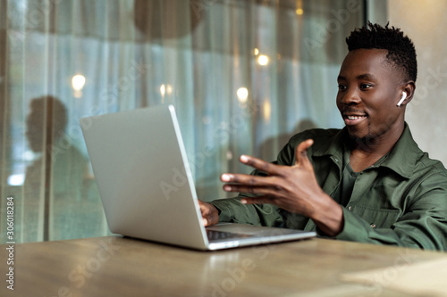 Handsome african american man using computer and smiling. Online video chat with business partners