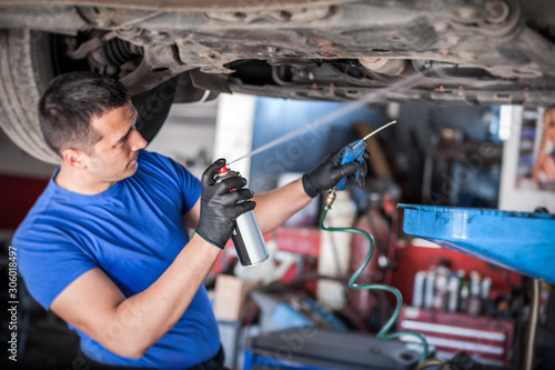 Photo Car master mechanic repairer lubricates screws with machine cleaner spray