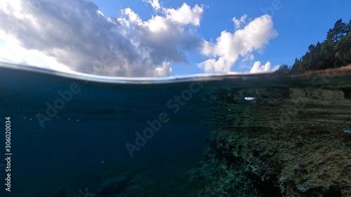 Fotografía  Beautiful underwater split above and below photo of rocky seascape with deep blu