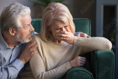 Elderly spouses indoors desperate wife crying worried husband comforting her Wallpaper Mural