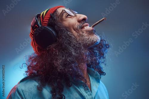 Fotomural Studio portrait of African Rastafarian male enjoys music in headphones and smoking weed