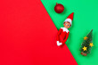 canvas print picture - Christmas background. Toy Santa elf, little Xmas tree, red bauble ball on red and light green background. Top view