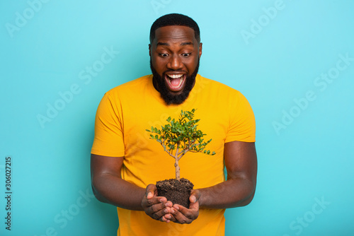 Happy surprised boy hold a small tree ready to be planted. Concept of forestation