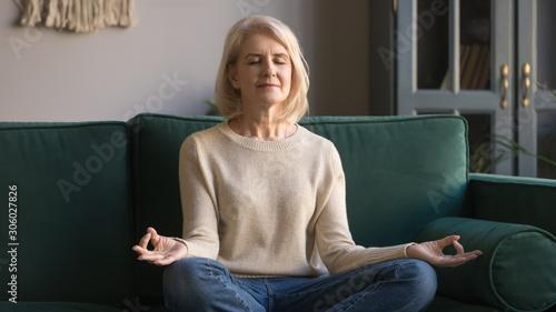 Spoed Foto op Canvas Wanddecoratie met eigen foto Serene elderly woman sit in lotus position meditating at home