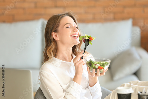 Slika na platnu Woman eating healthy vegetable salad in office