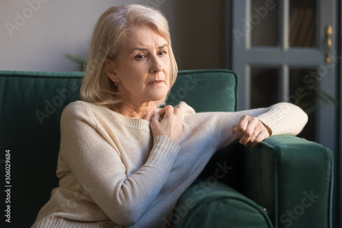 Mature depressed woman lost on thoughts sitting on couch Canvas Print