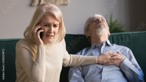 Leinwand Poster Wife makes emergency call while husband lies with heart attack