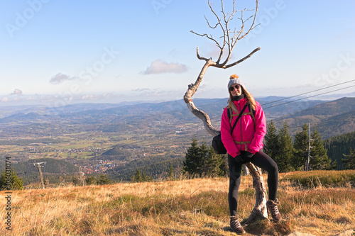 Fototapeta Young girl in pink jacket and dead tree in mountains. obraz